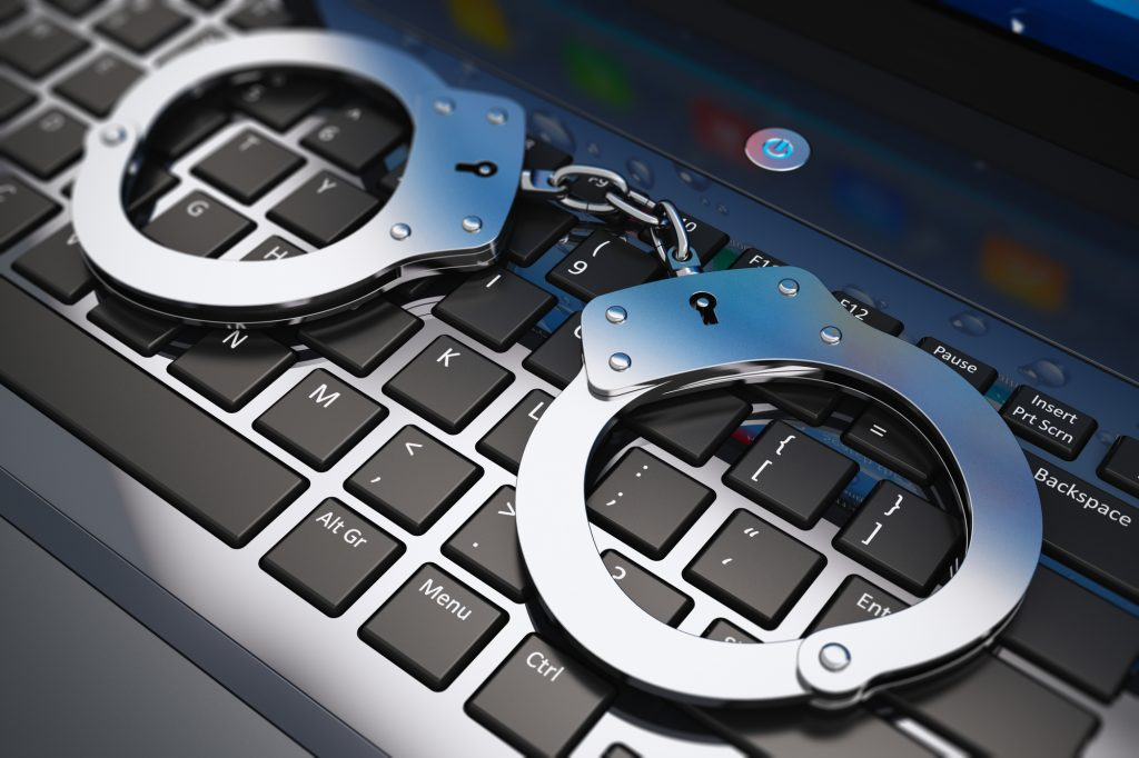 Creative abstract cyber crime, online piracy and internet web hacking concept: macro view of metal handcuffs on laptop notebook keyboard with selective focus effect
