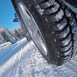 View of spinning car tire, driving on a snowy country road on a beautiful sunny day